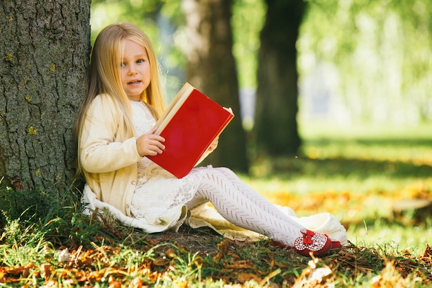 Cute little blonde girl sits near tree, reads favorite book and dreams