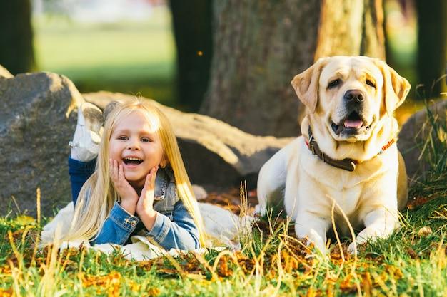 森の芝生の上の犬と一緒に座っているかわいいブロンドの女の子
