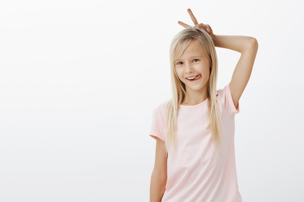 Cute little blonde girl smiling and make bunny ears with fingers behind head