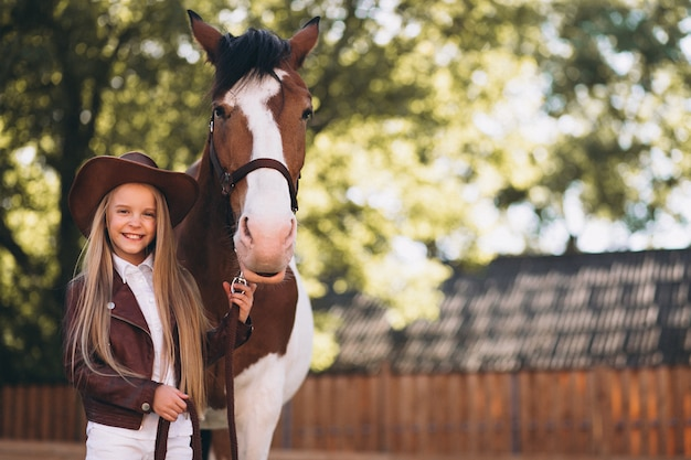 牧場で馬とかわいいブロンドの女の子