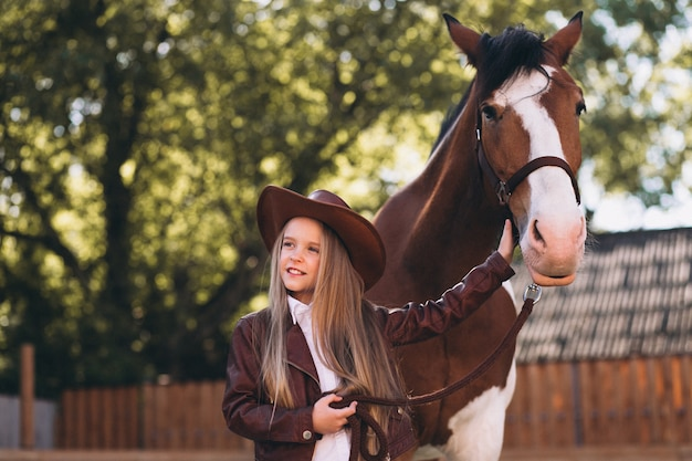 Cute little blonde girl with horse at ranch