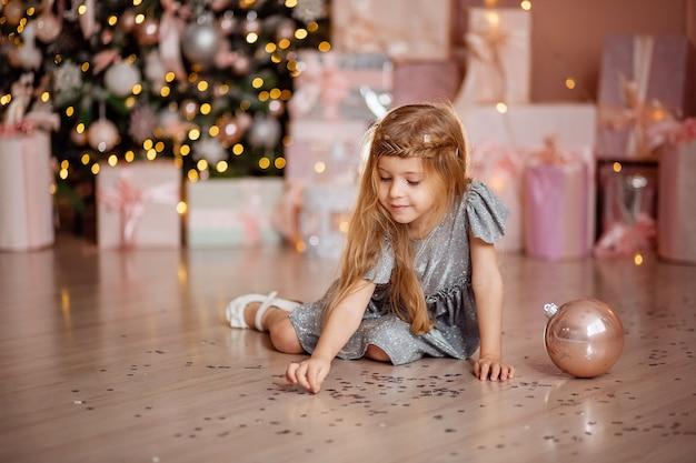 배경에 바닥에 사탕을 가지고 노는 긴 머리를 가진 귀여운 금발 소녀