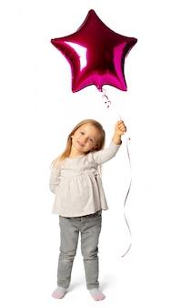 Милая маленькая белокурая девушка с фиолетовым воздушным шаром в форме звезды