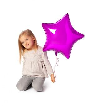 分離された紫色の星形の風船とかわいい小さなブロンドの女の子