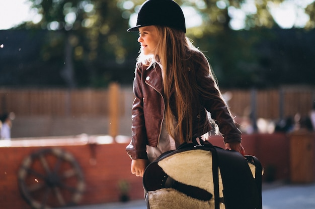 Cute little blonde girl with saddle in a stable