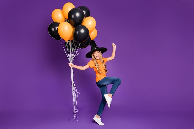Cute little blonde girl with a witch hat and balloons