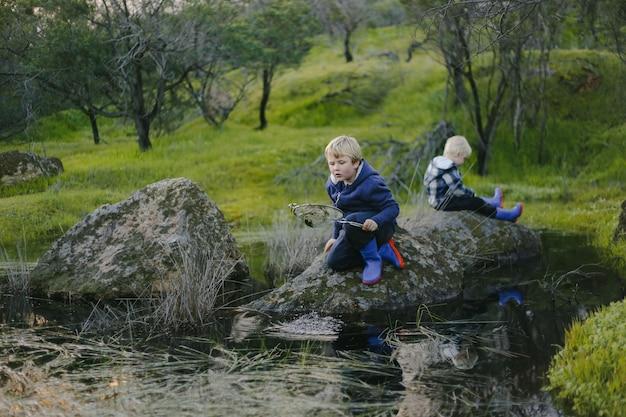 公園の岩の上に座っているかわいい金髪の子供たち