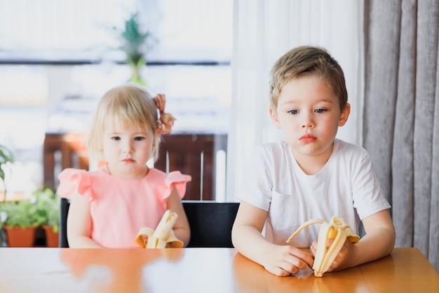 Милый маленький мальчик и девочка ест банан