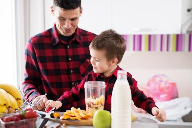 Милый маленький мальчик и его заботливый отец делают смузи в яркой кухне.