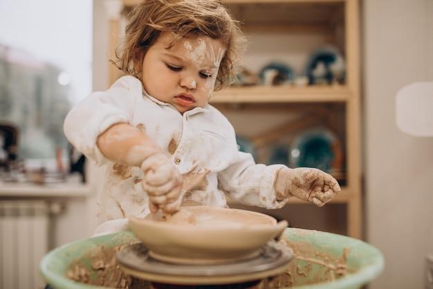 Милый маленький мальчик в классе гончарного дела