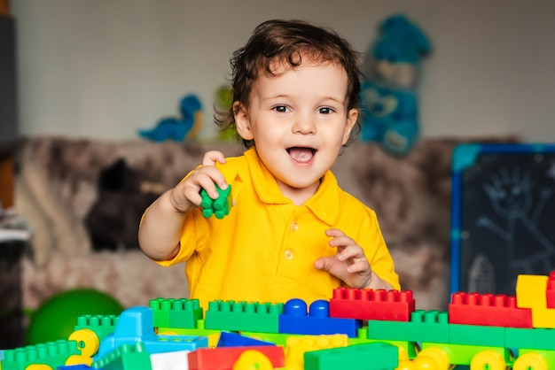 Cute little boy child playing at home with colorful cubes