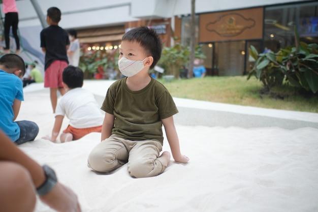 Covid19 발병 새로운 정상적인 생활 방식 동안 공공 놀이터에서 모래 상자 모래밭에서 노는 보호 의료 얼굴 마스크를 쓴 귀여운 소년