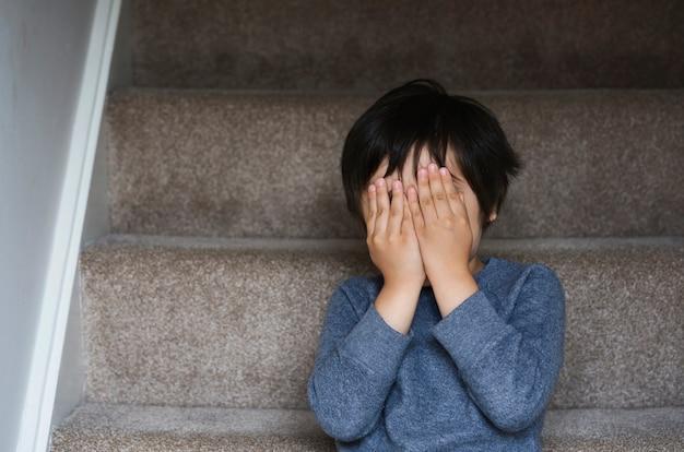 かわいい少年は、階段の上に座っている目をカバーしている数字を再生する数を隠す