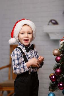 Милый маленький мальчик украшает елку в интерьере елочными игрушками