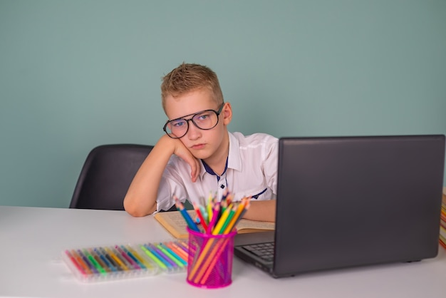 Милый маленький мальчик делает домашнее задание дома онлайн