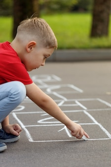 Cute little boy drawing hopscotch with white chalk on playground. activity game for kids on playground outside.