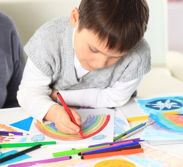 Милый маленький мальчик рисует в своем альбоме