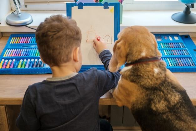 Милый маленький мальчик рисует фломастерами, сидя за столом. собака бигль сидит смешно рядом со мной