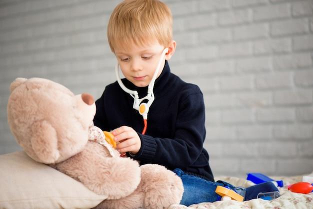 家でおもちゃのクマと遊ぶ医者に扮したかわいい男の子。