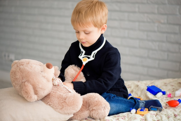 Cute little boy dressed as doctor playing with toy bear at home.