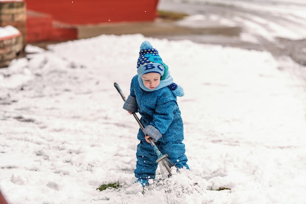 Cute little boy dressed in blue winter clothing playing with hay-fork on the snow.