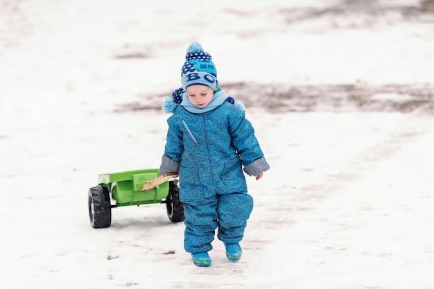 Милый маленький мальчик в синей зимней одежде, волоча трейлер игрушкой по снегу.