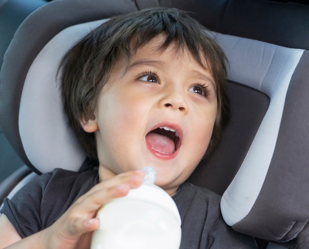 Cute little boy drinking milk bottle in a car seat while travel