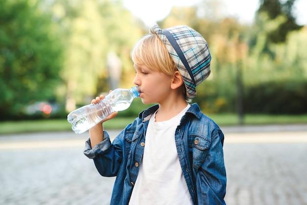ペットボトルから水を飲むかわいい男の子。子供は屋外で水を飲みます。路上でミネラルウォーターを飲む子供。健康な子供時代。