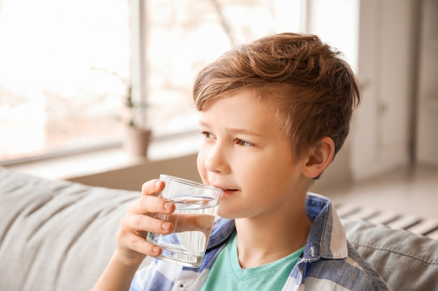 Cute little boy drinking water at home