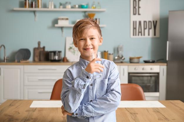 Милый маленький мальчик пьет воду на кухне