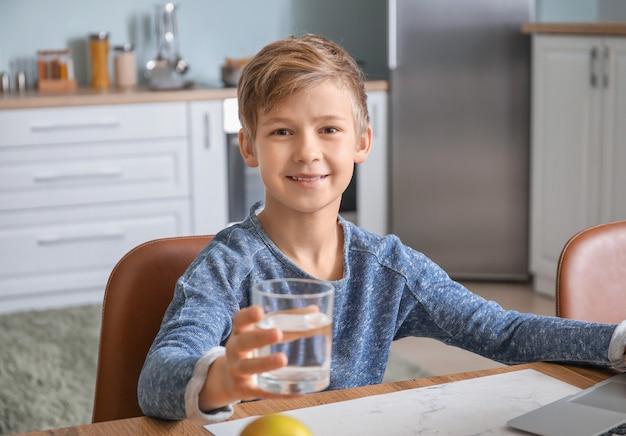 Cute little boy drinking water in kitchen