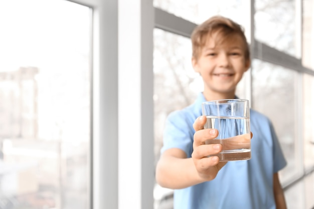 Милый маленький мальчик пьет воду возле окна