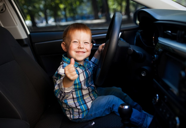 Cute little boy driving fathers car