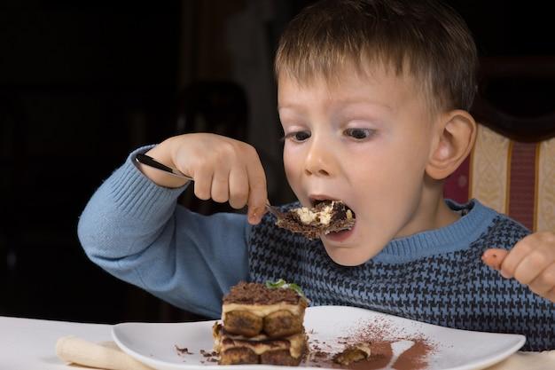チョコレートケーキを食べているかわいい男の子は、テーブルに座っているときに熱心な期待の表情で大きな一口を取りそうです
