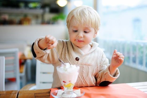 Cute little boy eating ice-cream (gelato) in italian indoors cafe. sweets/sugar food for little kids
