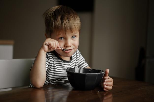 부리로 오트밀을 먹는 귀여운 소년