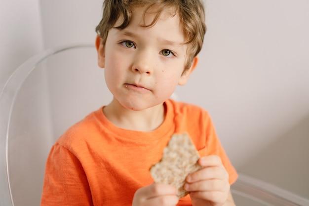 귀여운 소년은 크리스피브레드의 건강한 생활 방식과 영양 개념을 먹습니다