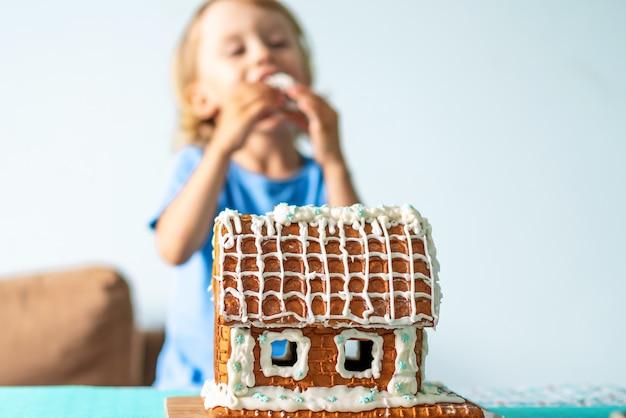 Cute little boy eats gingerbread house