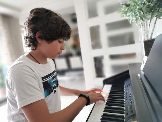 Милый маленький мальчик элегантно одетый играет на концертном пианино