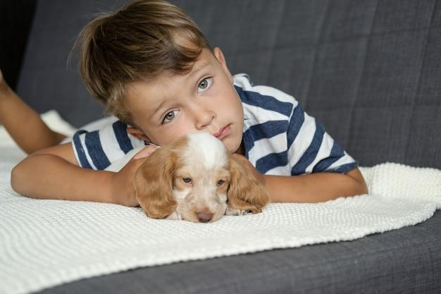 귀여운 어린 소년이 흰색 담요에 러시안 스패니얼 빨간색과 흰색 강아지 얼굴을 안고 키스합니다. 애완 동물 관리와 친절한 개념. 인간과 동물의 사랑과 우정.