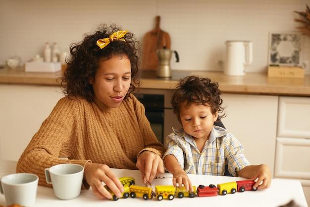 朝食時に台所のテーブルで彼の陽気な母親と一緒に座ってゲームを楽しんでいるかわいい男の子。彼女の愛らしい息子と遊んでいる若いラテン女性の家族の肖像画。子供の頃、ゲームと想像力