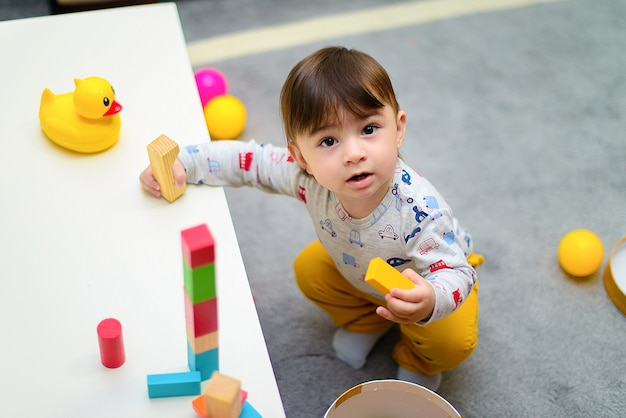 Cute little boy enjoying while playing with toys or blocks at his room