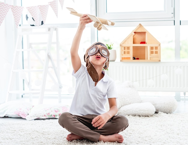 플레이 룸에서 바닥에 앉아 나무 비행기를 비행하는 귀여운 어린 소년