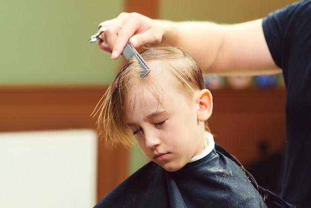 理髪店で美容師に散髪されているかわいい男の子。子供に髪型をしている床屋の男。はさみで美容師。理髪店。子供時代。少年のための新しい髪型。