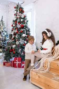 Cute little boy and girl playing near christmas tree and light on background. merry christmas and happy holidays.