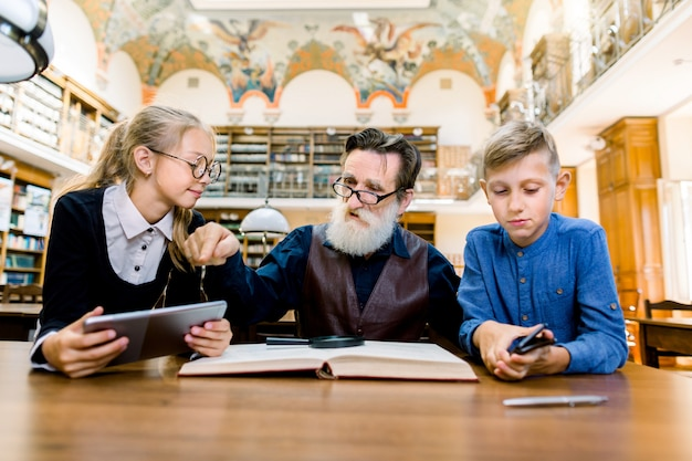 Cute little boy and girl study together with their grandfather, reading book