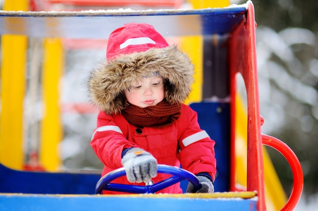 Cute little boy having fun on playground. winter outdoors fun for toddler kids