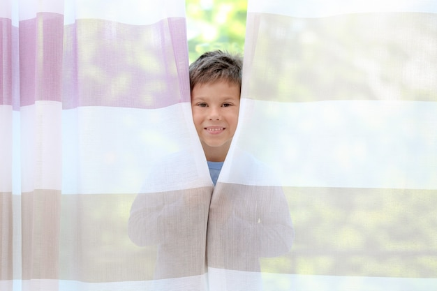 집에서 커튼 뒤에 숨어있는 귀여운 소년