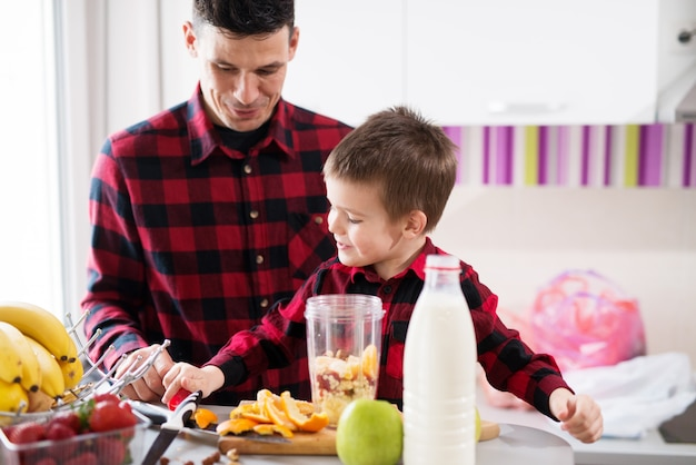 Cute little boy and his caring father are making a smoothie in a bright kitchen.