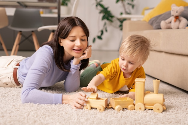 Cute little boy and his young pretty mother lying on fluffy rug on the floor of living-room and playing with wooden train after dinner